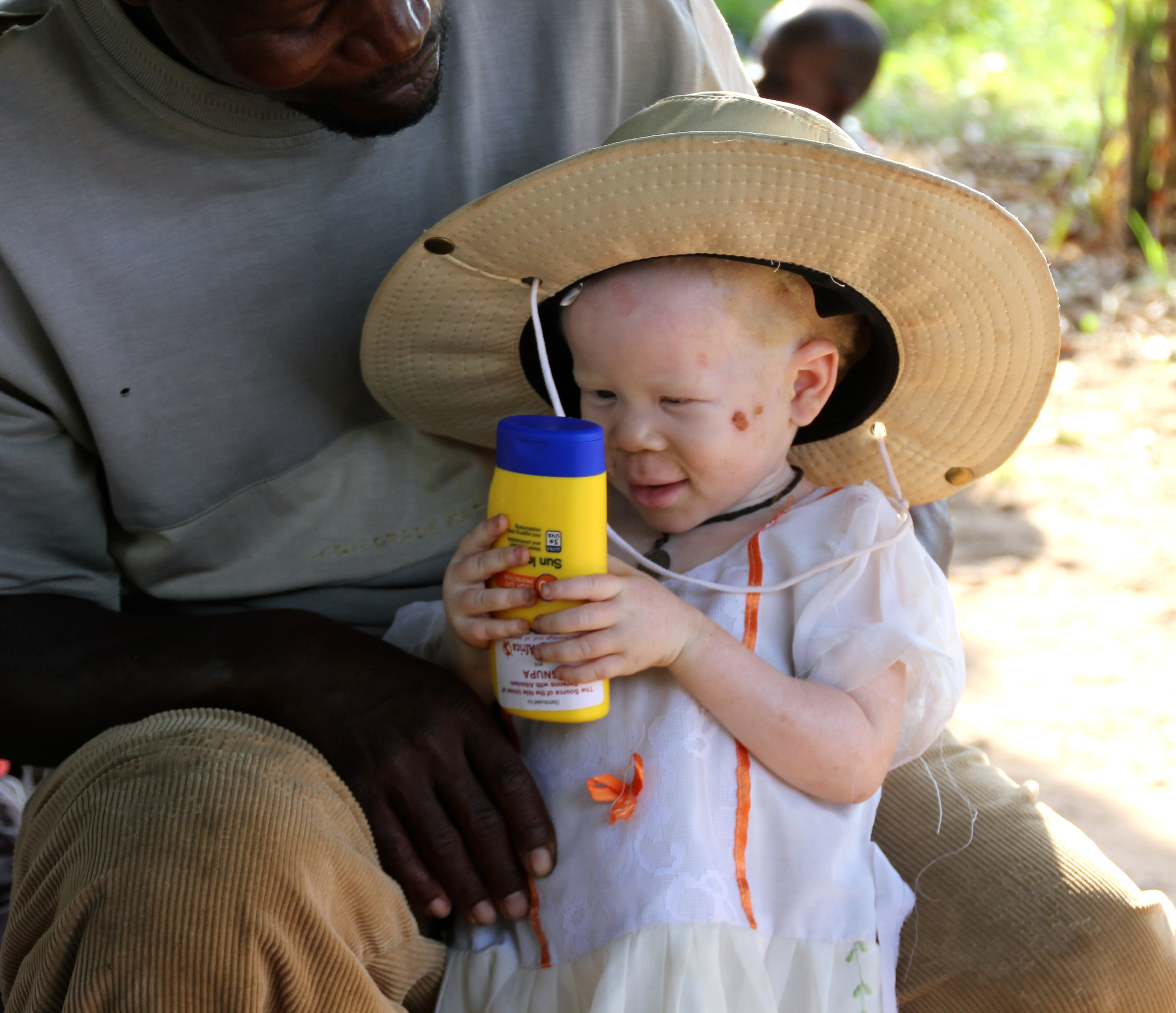 Baby holds her bottle of sunscreen